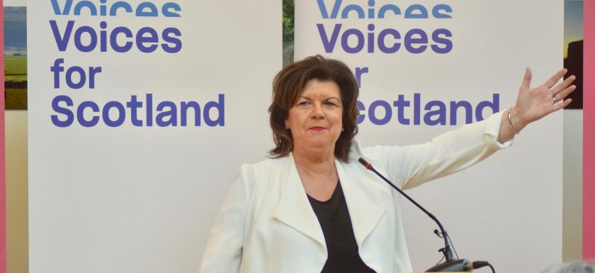 Elaine C Smith standing in front of a Voices for Scotland banner